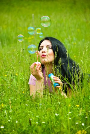Beautiful brunette woman lying in green spring  grass on a field and blowing soap bubbles photo