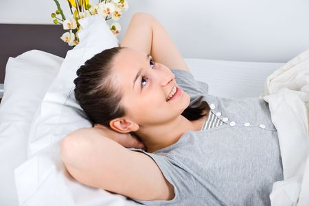 Cheerful relaxed young woman relaxed on bed with hands under head