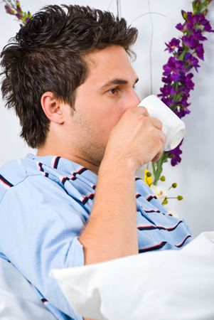 nightclothes: Profile of young man in bed drinking a cup of coffee in the morning
