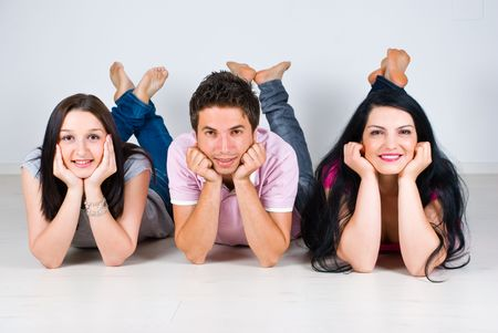 lying down on floor: Three friends lying  down on laminate flooring in a row with legs up and holding hands on  faces