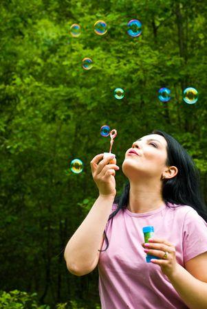 burbujas de jabon: Hermosa mujer de pie cerca de un bosque verde y t soplando muchas burbujas de jab�n coloridas, copiar el espacio para el mensaje de texto Foto de archivo