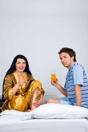 nightclothes: Couple sitting on bed and drinking glass with orange juice in the morning