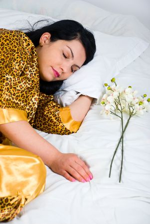 Beautiful woman sleeping on bed and having flowers near her photo
