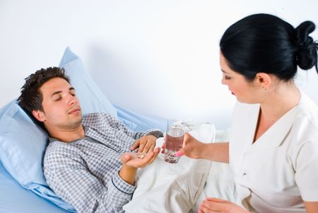 Nurse giving pills and glass with water to a male patient lying on a hospital bed photo