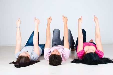 Group of three friends lying on back and giving all thumbs up photo