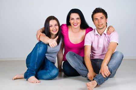 Three friends sitting on floor together in a embrace and showing thumbs photo