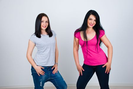 Two beautiful women posing in blank shirts and modern jeans photo
