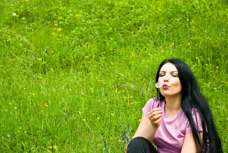 Beautiful brunette woman blowing dandelion and sitting on green grass in a field,copy space for text message on grass photo