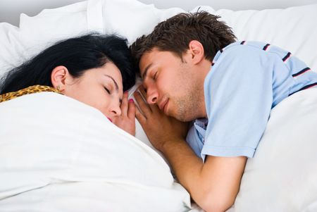 Close up of sleeping young couple face to face and touching hands photo