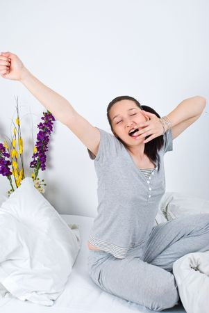 Young woman stretching and yawning in the morning or before sleep on her bed photo