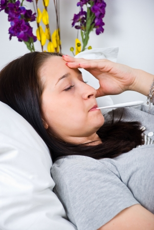 Sick woman checking temperature and lying on bed with hand on head Stock Photo - 6960588