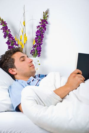 nightclothes: Young man relaxing on bed and reading a book