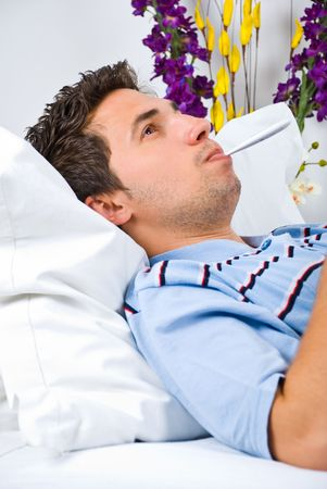 Sick man lying on bed and checking his temperature photo