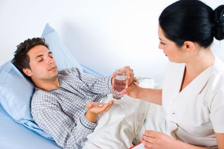 trustful: Nurse giving pills and glass with water to a sick male patient in hospital Stock Photo