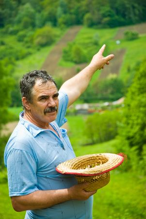 Farmer holding his straw hat and  showing plowing land on hills at countryside a green area with cultivated land and many forest photo