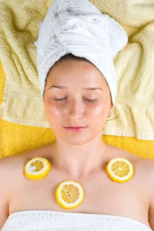 tratment: Young woman enjoying a therapy with slice lemon on her body skin at spa salon