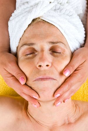 Senior woman receiving a facial massage at spa resort photo