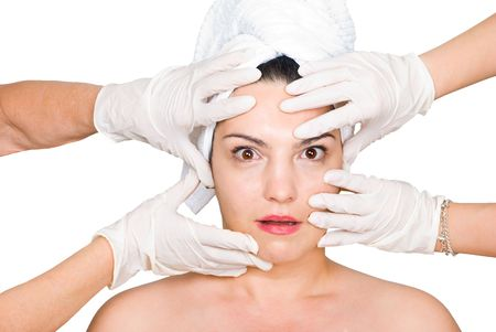 Hands with latex gloves touching a  surprised woman face preparing her for  surgical procedure with botox on white background, photo