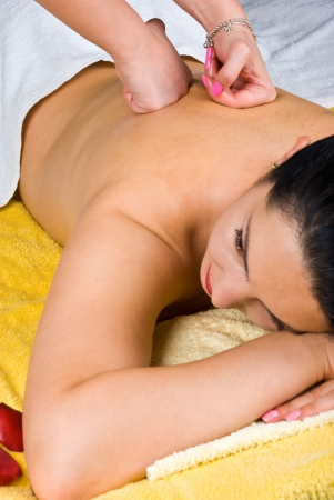 Young woman lying and receiving a back massage at spa salon Stock Photo - 7040582