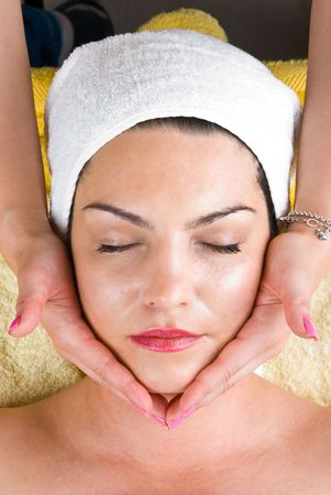 Beautiful woman at daily spa receiving a facial massage from a professional beautician photo