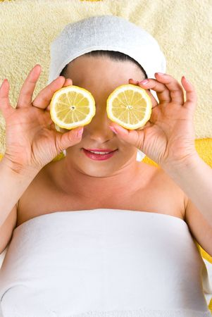 Happy woman at spa resort showing two slices lemon photo