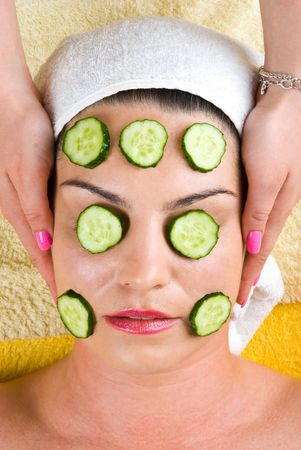 Beautician making a facial mask with slice  cucumber to a young woman and holding her hands on client head Stock Photo - 7040588