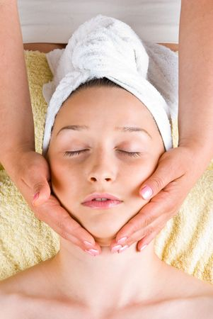 Young woman receiving a facial massage at spa retreat photo
