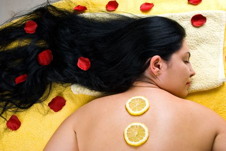 Top view of beautiful woman with long hair lying on massage table and having  slice lemon treatment on her back and rose petals in hair photo