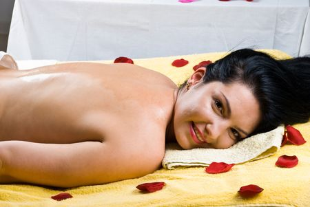 Happy smiling woman lying on massage table and having her back with oil photo