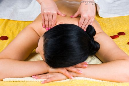 tratment: Brunette woman at spa salon getting a shoulders  massage from a professional masseuse Stock Photo