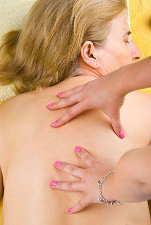 Senior woman getting a back massage in a spa salon photo