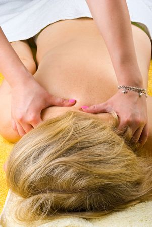 Senior woman getting a deep massage on shoulders at spa resort photo