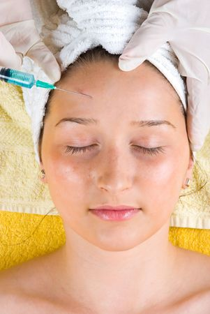 Young woman getting a botox injection to forehead  and lying with eyes closed Stock Photo - 7040688