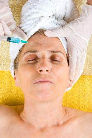 Senior woman getting cosmetic treatment with botox injection photo