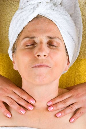 Aged woman lying with eyes closed and getting a neck massage in a spa salon photo