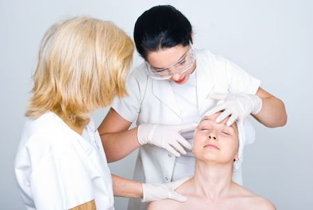dermatology: Two doctors women consulting a patient woman  skin and the young doctor pointing  and showing something  on patient face to her colleague  and preparing for botox treatment procedure Stock Photo