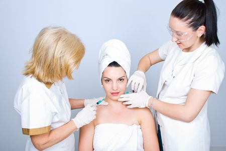 Two plastic surgeons giving botox injection to a young  woman skin  photo