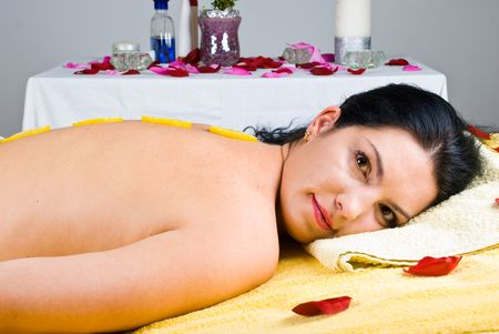 Beautiful woman relaxing at spa salon and having slices lemon on her back skin photo