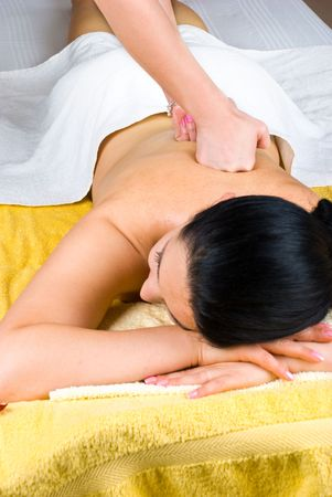 Young female receiving a deep massage on back at spa salon photo
