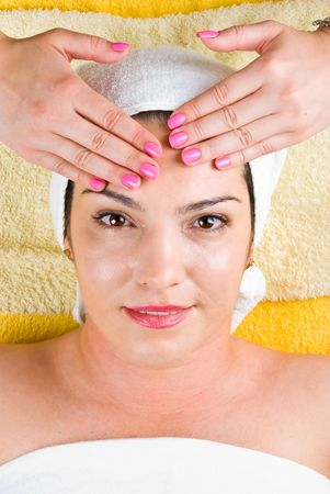 Attractive woman getting a facial massage at spa salon and  looking happy photo