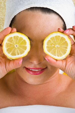 Healthy woman holding  slices lemon at spa salon and smiling Stock Photo - 7040689