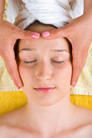 Beautiful young woman getting head massage at spa salon photo