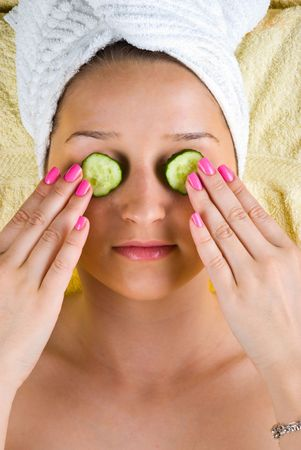 Beautiful young woman holding slices cucumber on her eyes at spa center Stock Photo - 7040692