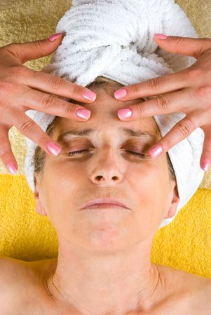 Senior woman lying with eyes closed and receiving a facial massage  at spa resort photo