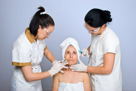 Two young plastic doctors injecting botox or acid hyaluronic to a senior woman forehead and mouth  photo