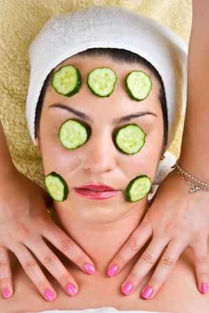 Young woman with cucumber mask getting a neck massage from a masseuse at spa salon photo