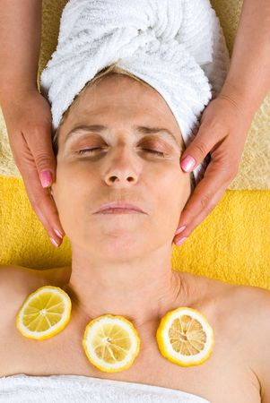 Senior woman having a treatment with slices lemon on her chest and a beautician holding hands on her head at spa salon photo