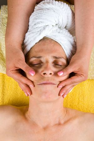 Senior woman getting a facial massage on cheeks at spa salon photo