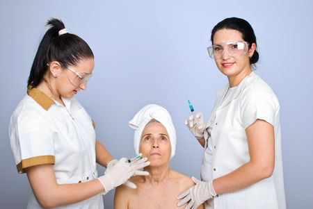 Doctor inject botox to senior woman cheek and the other doctor holding a syringe and smiling photo