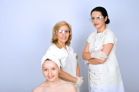Young woman patient in front of image with  two women plastic surgeon standing with hands crossed  and smiling photo